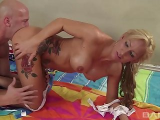 Tattooed blonde with fake knockers moans while getting her asshole smashed
